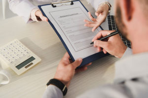 cropped-view-of-client-signing-insurance-claim-for-VS8PD3Q