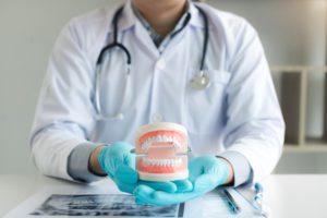 dentist-holding-dentures-in-office-room-TM38LES (1)